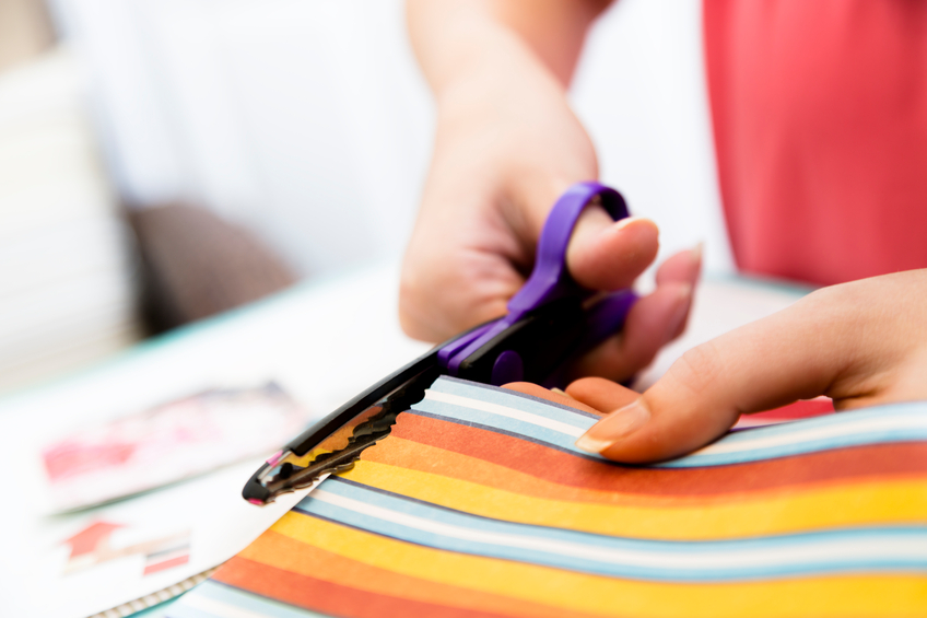 Art and Craft: Woman cutting paper for scrapbooking. Domestic hobby
